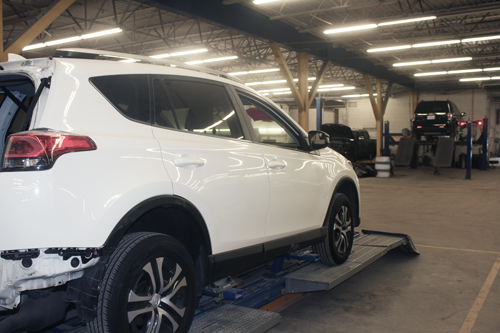 White SUV on frame alignment machine in foreground and black SUV on wheel alignment machine in the background