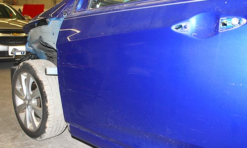 Blue car in shop with front quarter panel removed